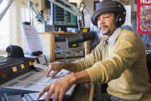 Mixed race disc jockey using control panel in studio